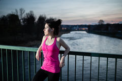 Young woman having break. After jogging at sunset in the city on the bridge cross the river. Girl running outdoors in a city park. Color toned image royalty free stock photography