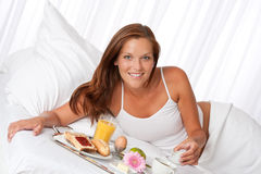 Young woman having breakfast in bed Stock Images