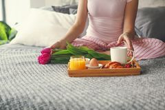 Young woman having breakfast in bed stock photography