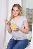 Young woman having breakfast with corn flakes at home Royalty Free Stock Photography