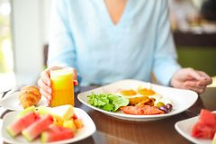 Young woman having breakfast with fried eggs. Orange juice and fruits Royalty Free Stock Photography