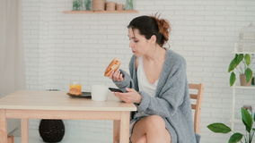 Young woman having breakfast in kitchen and browsing Internet, using smartphone. Girl eats the croissant, drinks coffee. Young woman having breakfast in kitchen stock video footage