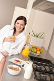 Young woman having breakfast in modern kitchen Stock Photos