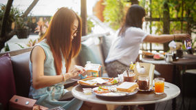 Young woman having breakfast in outdoor cafe at chiangmai city Thailand ,soft focus Stock Photography