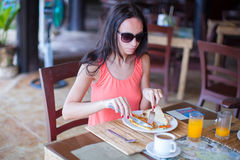 Young woman having breakfast at outdoor cafe Stock Photos