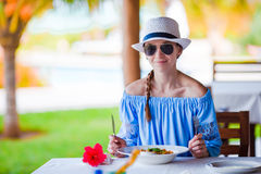 Young woman having breakfast at outdoor cafe on summer vacation Stock Photo