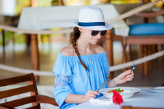 Young woman having breakfast at outdoor cafe on summer vacation Stock Image