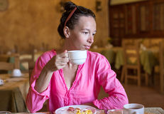 Young woman having breakfast at resort restaurant Stock Photos