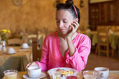 Young woman having breakfast at resort restaurant Stock Images