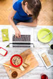 Young woman having breakfast while using a laptop computer Stock Photo