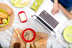 Young woman having breakfast while using a laptop computer Stock Images