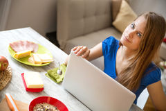 Young woman having breakfast while using a laptop computer Royalty Free Stock Photography