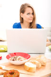Young woman having breakfast while using a laptop computer Stock Photography