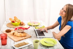 Young woman having breakfast while using a laptop computer Stock Image