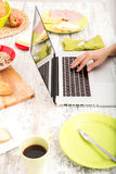 Young woman having breakfast while using a laptop computer Royalty Free Stock Photo