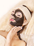 Young woman  having clay body mask. Stock Photos