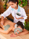 Young woman  having clay body mask. Royalty Free Stock Photos