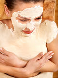 Young woman  having clay body mask. Stock Photo