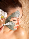 Young woman  having clay body mask. Royalty Free Stock Image