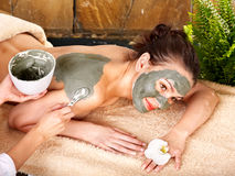 Young woman having clay body mask.