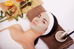 Young woman having clay skin mask treatment on her face. Applying facial mask at woman face at beauty salon Royalty Free Stock Photos