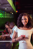 Young woman having cocktail at bar counter Stock Photo
