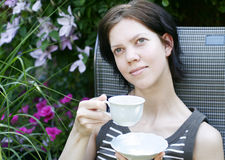 Young woman having coffee. In the garden in summer stock photos
