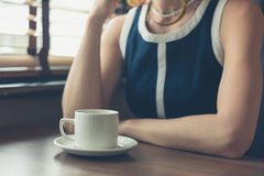 Young woman having coffee in diner. A young woman is sitting by the window in a diner and is having a cup of coffee Stock Image