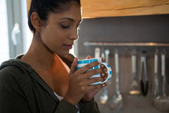 Young woman having coffee. In kitchen Royalty Free Stock Photos