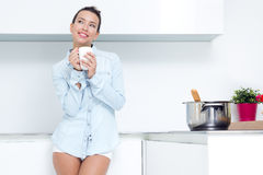 Young woman having a coffee at the kitchen Stock Photo