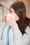 Young woman having coffee or tea in the kitchen Stock Photo
