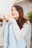 Young woman having coffee or tea in the kitchen Stock Images