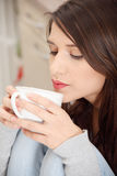 Young woman having coffee or tea in the kitchen Royalty Free Stock Photography