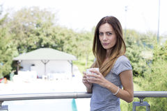 Young woman having a coffee on terrace Royalty Free Stock Images