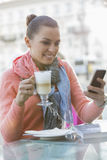 Young woman having coffee while using cell phone at sidewalk cafe Royalty Free Stock Photos