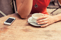 Young woman having coffee and using phone Stock Image