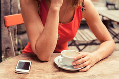 Young woman having coffee and using phone Royalty Free Stock Photo