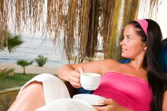 Young woman having a cup of coffee in bungalow Stock Images