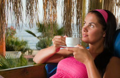 Young woman having a cup of coffee in bungalow Royalty Free Stock Image