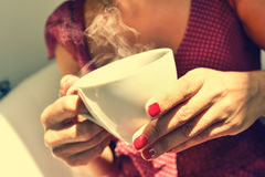 Young woman having a cup of tea or coffee Stock Photos