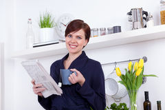 Woman having a cup of tea and reading the newspaper Stock Photos