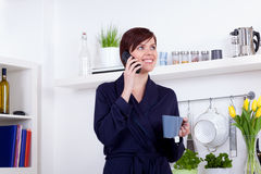 Woman having a cup of tea and talking on the phone Stock Photo