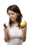 Young woman having a dilemma. Young woman choosing between healthy and junk food Stock Images
