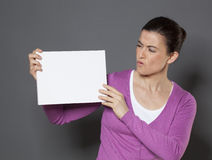 Young woman having doubts in message written on a white board Royalty Free Stock Photos