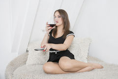 Young woman having a drink on sofa while changing channels with remote control Royalty Free Stock Photos
