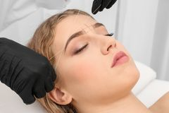 Young woman having eyebrow correction procedure. In beauty salon Royalty Free Stock Photography