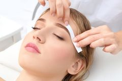 Young woman having eyebrow correction procedure. In beauty salon Royalty Free Stock Image