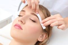 Young woman having eyebrow correction procedure