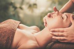 Young woman having face massage in a spa salon Stock Photos