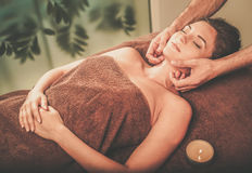 Young woman having face massage in a spa salon Stock Image